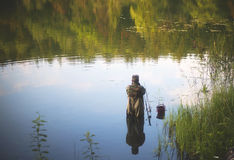 Fisherman. Standing in water and fishing on late evening Royalty Free Stock Photos