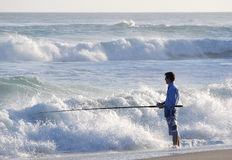 Fisherman standing in water Stock Images