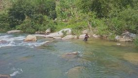 Fisherman Stands on Bank and Pulls Net among Rapids stock video footage