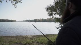 Fisherman stands with a fishing rod on the river bank and looks at the water and a bird flying over the water. Slow. Fisherman stands with a fishing rod on the stock footage
