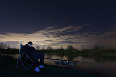 Fisherman in Starry Night, Sitting in chair looking on rods, patience Royalty Free Stock Photo