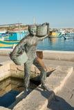 Fisherman statue. On embankment of famous Marsaxlokk village, Malta Royalty Free Stock Photo