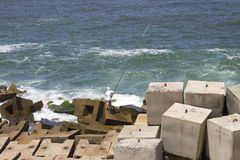 Fisherman on the stony sea shore in Alexandria Stock Photos