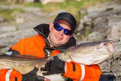 Fisherman in sunglasses holds a big fish stock photos