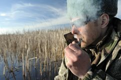 Fisherman with sunglasses is smoking tobacco-pipe on the Lake at springtime Stock Photo