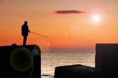 Fisherman at sunrise. On the sea Stock Image