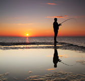 Fisherman at sunrise. On the sea Stock Photos