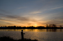 Fisherman at Sunrise. Man fishing from the river's edge at sunrise Stock Photo
