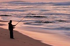 Fisherman at sunrise. Lone fisherman on the beach at sunrise stock image