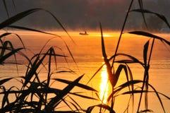 Fisherman at sunrise. On a big lake Royalty Free Stock Photos