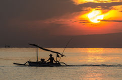Fisherman at sunrise in indonesia. Fisherman in boat at sunrise in indonesia stock photography