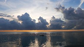 Fisherman at Sunrise. Silhouette of a fisherman paddling his traditional boat for the morning catch at sunrise. The sea is calm and the sky is colorful. in stock footage