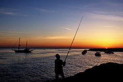 Fisherman by sunset Stock Photo