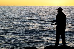 Fisherman at sunset. Silhouette of Fisherman at sunset - Cottesloe beach , Perth Stock Photos