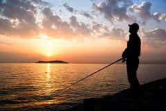 Fisherman by sunset Royalty Free Stock Photo