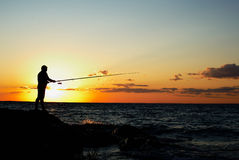 Fisherman at sunset. Silhouette of the fisherman at sunset Stock Images