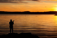 A fisherman in sunset. Royalty Free Stock Photos