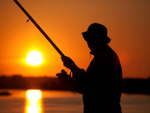 Fisherman on sunset. Silhouette of a fisherman on sunset Royalty Free Stock Photos