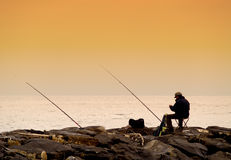 Fisherman at sunset. Lonely fisherman at sunset. Post-processed image with warm tones royalty free stock images