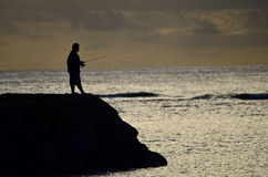 Fisherman at sunset on the beach Stock Images