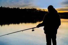 Fisherman at sunset fishing Stock Image