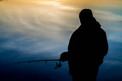Fisherman at sunset fishing Stock Photography