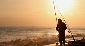 Fisherman at Sunset Hawaii. Fisherman at beach during Sunset- Hawaii Royalty Free Stock Images