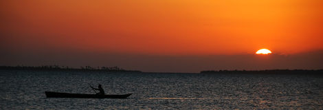 Fisherman in the sunset - Zanzibar. Fisherman on his way back home in Zanzibar (Tanzania) with a special colorful sunset royalty free stock photo
