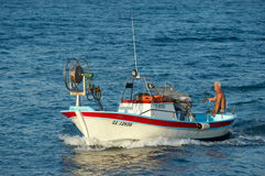 Fisherman swims on his fishing boat Royalty Free Stock Photography