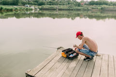 Fisherman and tackle box Stock Photo