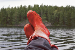 Fisherman taking a break with rubber boots resting on bulwark. Royalty Free Stock Images