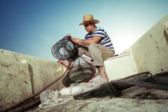 Fisherman taking out the fishing net Royalty Free Stock Photos