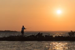 Fisherman throw in to the lake his bait. The fisherman throw in to the lake his bait. Action in the sunset stock photos