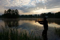 Fisherman. Throwing fishing bait during cloudy sunrise royalty free stock photo