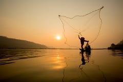 Fisherman throwing fishing net Stock Images