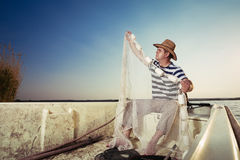 Fisherman throwing the net Stock Images