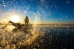 Fisherman throwing net at sunrise , Thailand stock photos