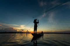 Fisherman throwing net in sunrise , Thailand stock photography