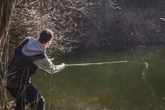 The fisherman throws a hook. Fishing, activity in nature, on the river. The fisherman throws a hook in clear water Royalty Free Stock Photo