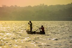 Fisherman throws a net in Lake Victoria. Fishermen cast a net in Lake Victoria at a bright sunset. Uganda stock images