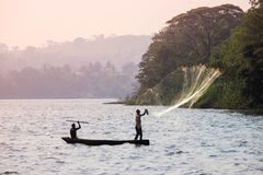 Fisherman throws a net in Lake Victoria. Fisherman at sunset throws a net into the waters of Lake Victoria royalty free stock photo