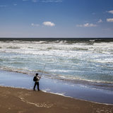 Fisherman at the Tide. Fisherman fishing at the tide on the beach with wild sea stock photography
