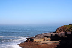 Fisherman on the tip. Shoreline view of rocky beaches near Sintra, Portugal Stock Photography