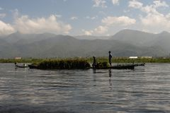 Traditional fisherman of Inle Lake. Fisherman in traditional costume fishing in balance, with a net, in a typical Inle lake canoe. Myanmar stock photo