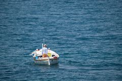 Fisherman in traditional wooden boat at sea royalty free stock photo
