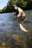Fisherman with trout in caught in net Stock Photos