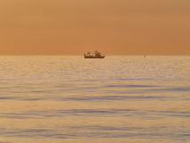 Fisherman trowing net from a small fishing boat at dusk, calm sea Stock Photos