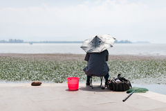 Fisherman with an umbrella on the head by a lake. Xichang, China Stock Photos
