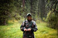 Fisherman under  summer snowfall in mountains Royalty Free Stock Image