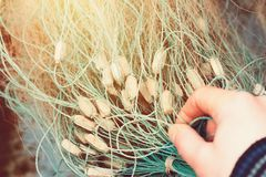 A fisherman untangles a fishing net at dawn. Close-up of tackle for fishing in warm sunlight royalty free stock image